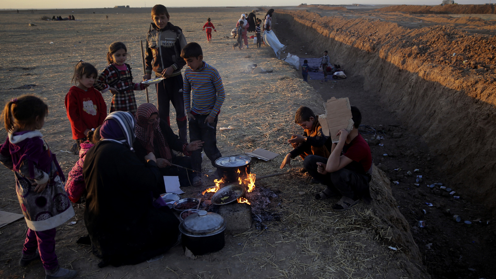 Families who fled ISIS cook next to a trench created by Kurdish forces to demarcate their border, as they wait to cross to the Kurdish areas, in the Nineveh plain, northeast of Mosul. The sand berms and trenches snake across northern Iraq into Syria, alongside newly paved roads and sprawling checkpoints decked with Kurdish flags, in what increasingly resembles an international border. (AP/Hussein Malla)