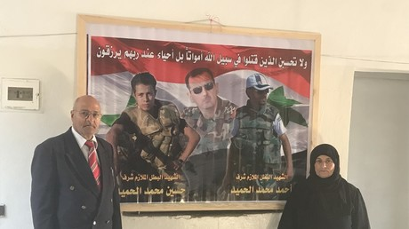 Mohammed Gabbash Al Hamid and his wife Fatima next to the photo of their martyrd sons in the SAA, Ahmed and Hussain. © Vanessa Beeley