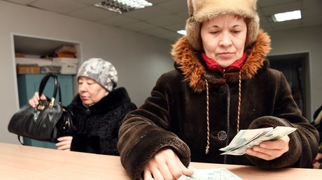 A woman counts the pension she received at a post-office in Chita © Evgeny Yepanchintsev