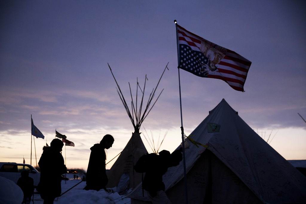 FILE - In this Dec. 4, 2016 file photo, travelers arrive at the Oceti Sakowin camp where people have gathered to protest the Dakota Access oil pipeline as they walk into a tent next to an upside-down american flag in Cannon Ball, N.D. It has been called the largest gathering of Native American tribes in a century. Tribal members and others have joined in an ongoing, tense protest against the $ 3.8 billion Dakota Access oil pipeline, which the Standing Rock Sioux believes threatens sacred sites and a river that provides drinking water for millions of people. The protest is included in the AP top news stories in North Dakota this year. (AP Photo/David Goldman File)