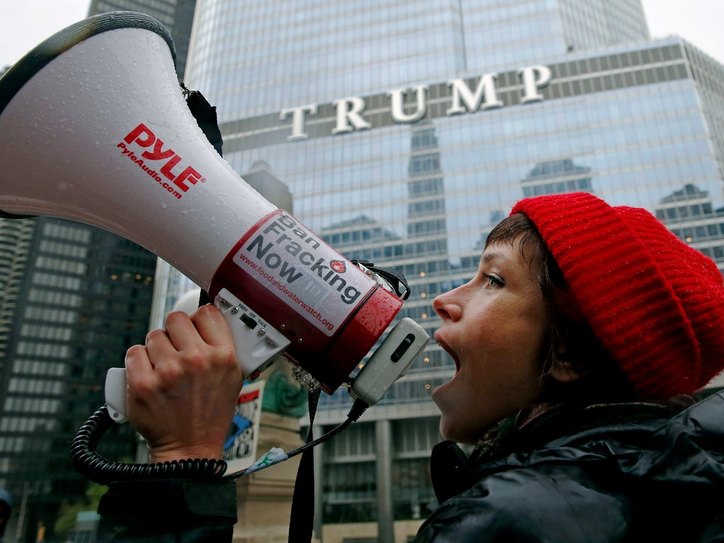 """Jessica Fujan chants on the Wacker Drive during a """"100 Days of Failure"""" protest and march, Saturday, April 29, 2016, in Chicago. Thousands of people across the U.S. are marking President Donald Trump's hundredth day in office by marching in protest of his environmental policies. (AP Photo/Nam Y. Huh)"""