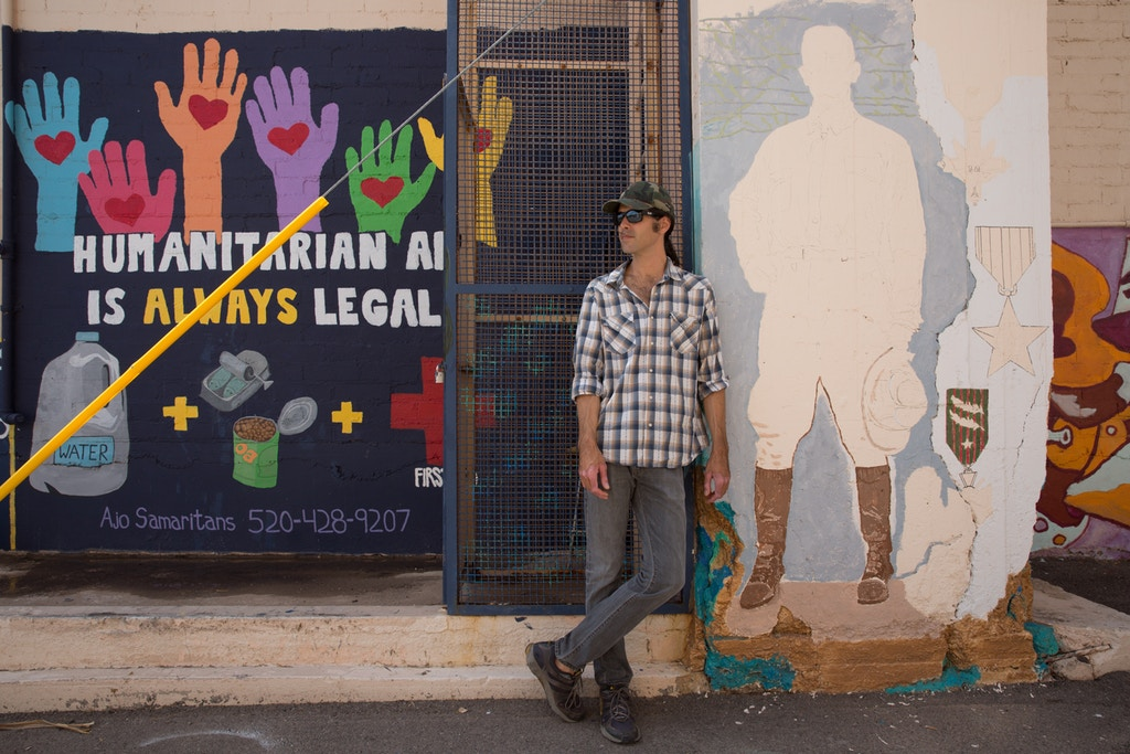 Scott Warren stands next to a community mural project created by the Ajo Samaritans, one of the humanitarian aid groups he works with in the region.
