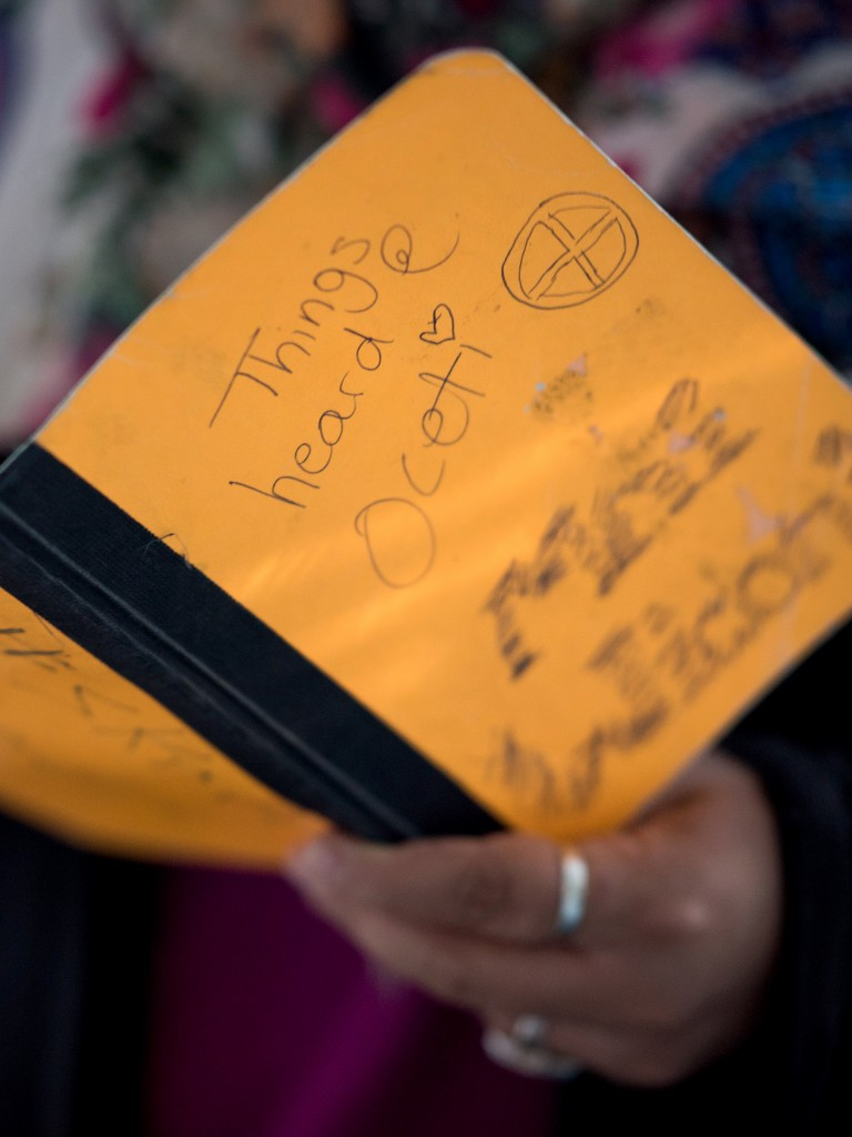 """CAPTION: Tala Ali, an anti-pipeline activist who was affected by the surveillance actions of security contractor TigerSwan, reads quotes from a notebook of """"Things Heard at Oceti"""" that she recorded during her time at Standing Rock at her home in Cincinnati, OH on Friday, September 28, 2018. (Emma Joy Howells for The Intercept)"""