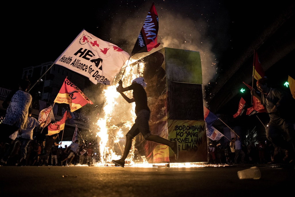 "TOPSHOT - Activists burn an effigy of Philippine President Rodrigo Duterte during a protest in Manila on December 10, 2017, as they commemorate the International Human Rights Day.  Philippine President Rodrigo Duterte on December 5 told human rights groups criticising his deadly anti-drug war to ""go to hell"" after ordering police back to the frontlines of the crackdown. / AFP PHOTO / NOEL CELIS        (Photo credit should read NOEL CELIS/AFP/Getty Images)"