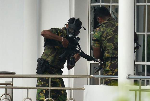 A member of the Sri Lankan Special Task Force (STF) pictured outside a house during a raid.