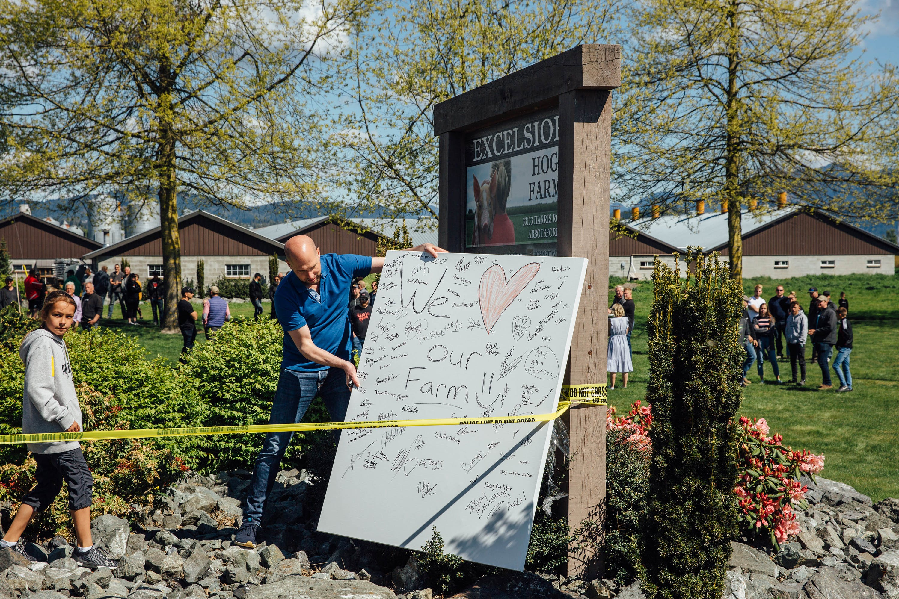Supporters of the Excelsior Hog Farm family create a sign with their signatures and place it at the entrance to their farm in Abbotsford, B.C. on April 28, 2019.