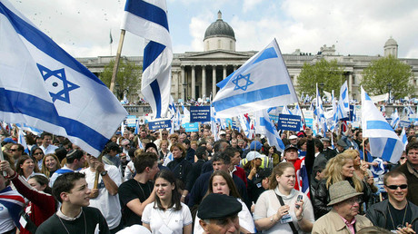 FILE PHOTO: Israeli flags are waved by demonstrators during an Israel Solidarity Rally in London's Trafalgar Square, on May 6, 2002. © Ian Waldie