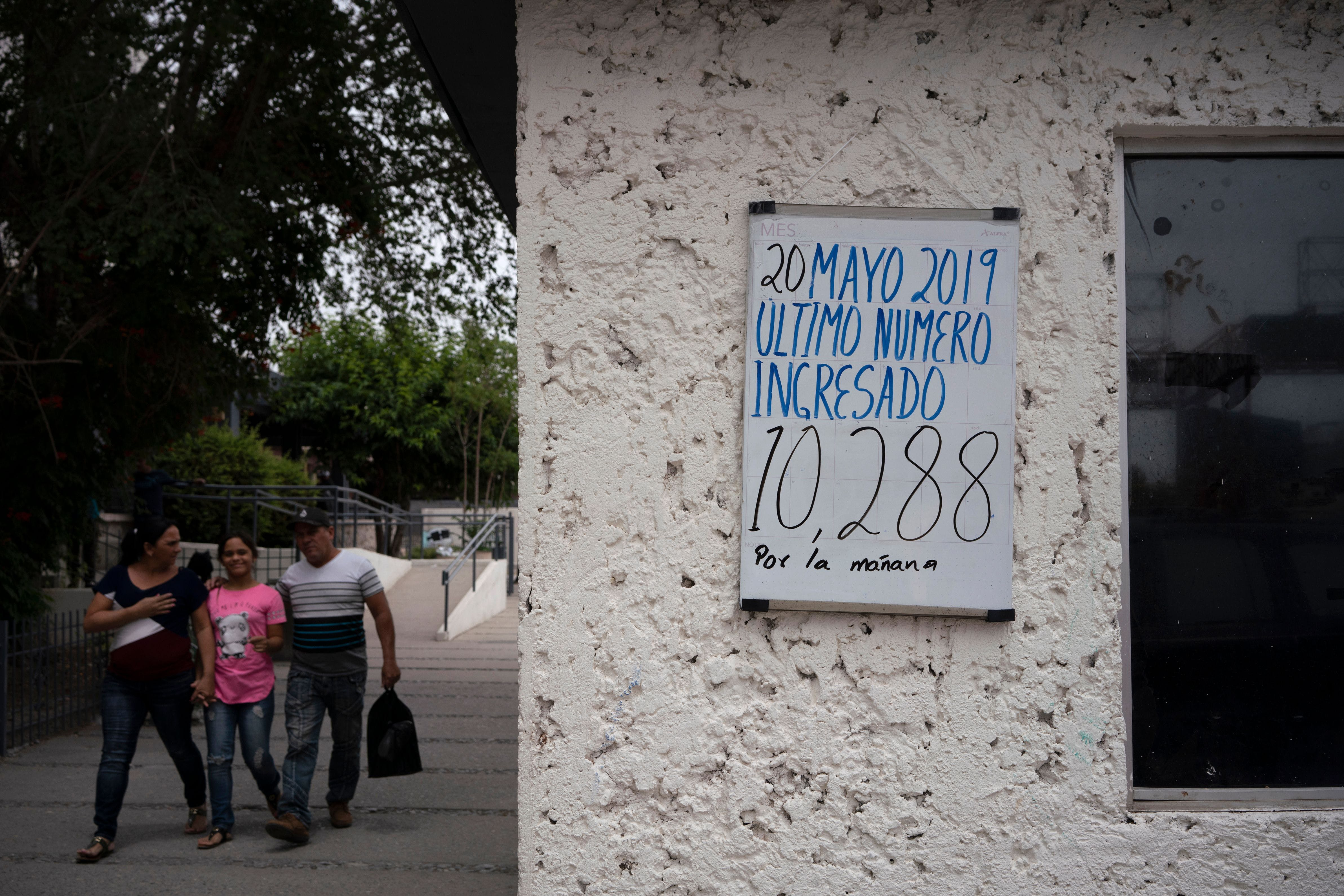 "People walk past a sign reading ""last number entered"" in Ciudad Juarez, Chihuahua state, on May 20, 2019. - About 7,000 migrants are waiting to enter the United States via El Paso, either by the metered number system, or those which are part of the remain in Mexico policy, Migrant Protection Protocols. Those that are part of MPP are made to wait out their asylum claims on the Mexican side of the Border, where they are vulnerable to criminals looking for an easy target, extortionists, corrupt police, among other dangers."