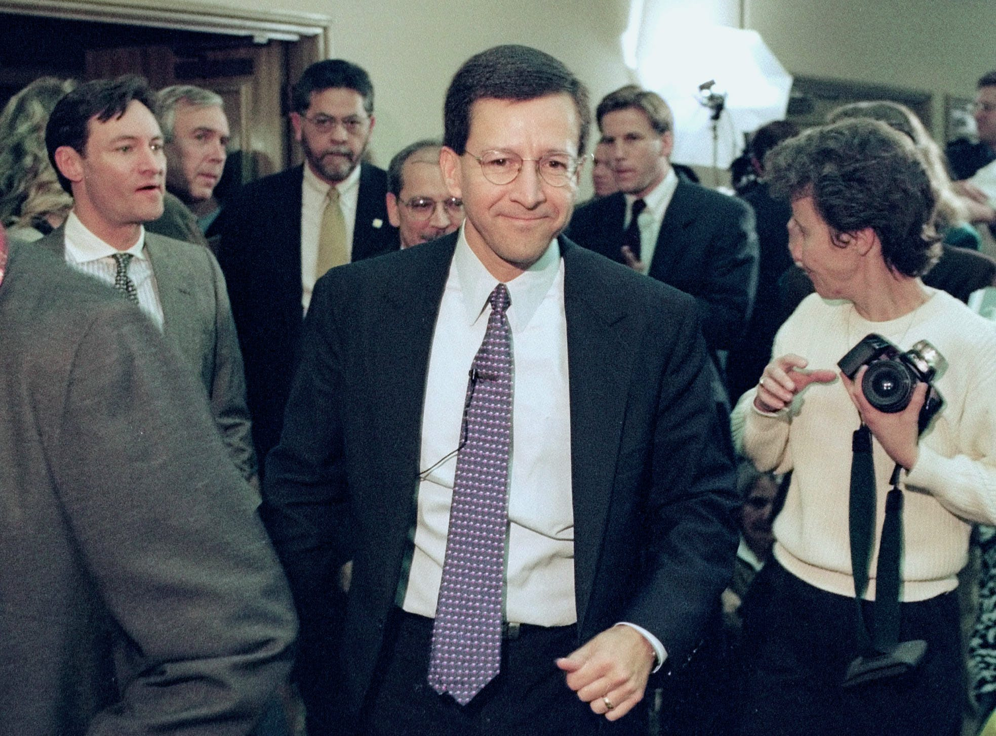 ** FILE ** Dan Morales, center, then Texas Attorney General, shown in this file photo from Jan. 16, 1998, moves through a crowd before his news conference to announce the award of $ 15.32 billion to the state from the tobacco industry. Former Texas Attorney General Dan Morales and a onetime law associate were indicted Thursday, March 6, 2003, on federal charges of trying to fraudulently obtain hundreds of millions of dollars in attorney fees from a state settlement with tobacco companies.  Both Morales and Marc Murr, a former associate and personal friend, were expected to turn themselves in Friday, authorities said. (AP Photo/Harry Cabluck, File)