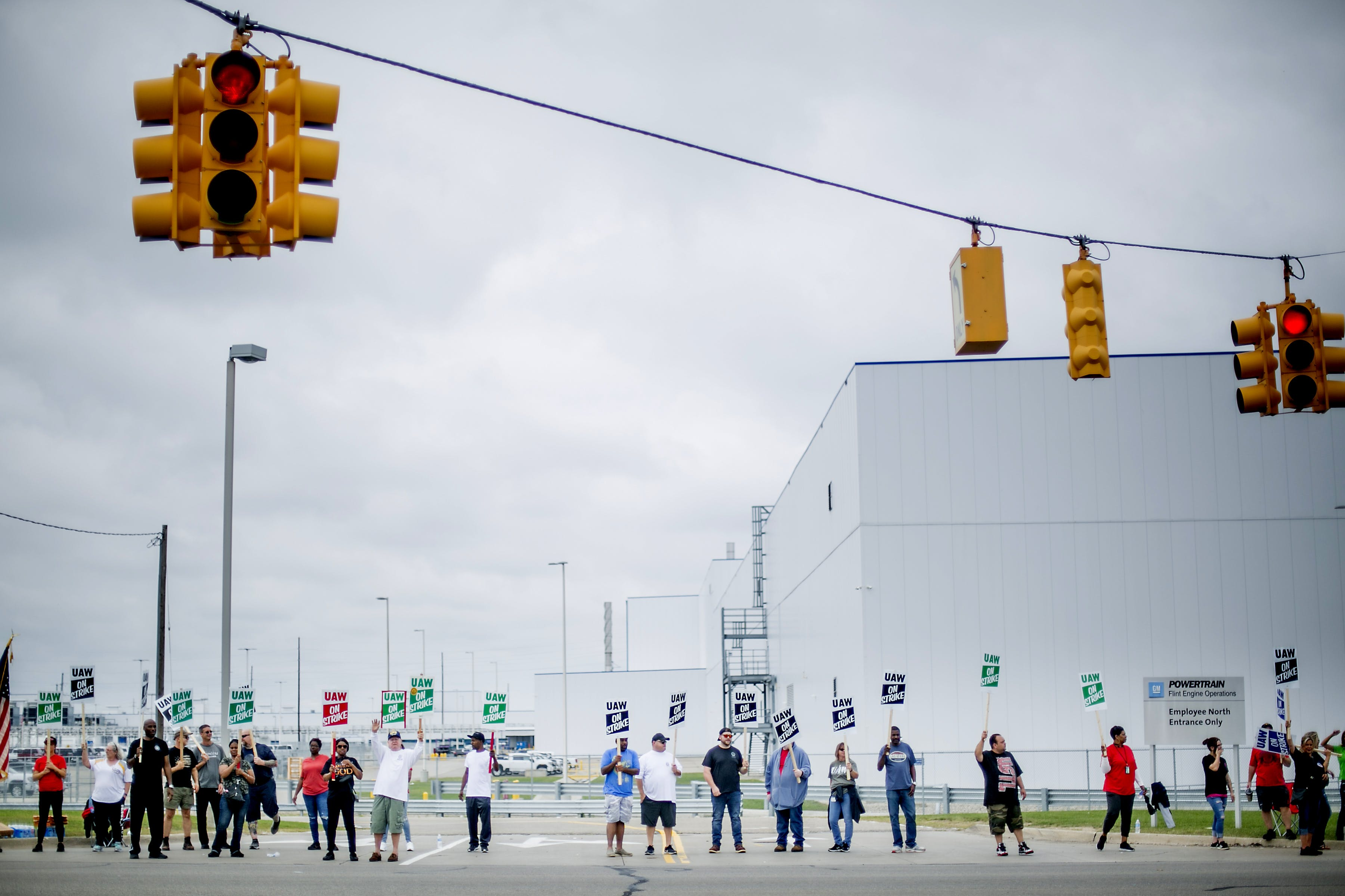 Demonstrators holds signs during a United Auto Workers (UAW) strike outside the General Motors Co. Flint Engine Operations plant in Flint, Michigan, U.S., on Monday, Sept. 16, 2019. The UAW union is leading its first strike against General Motors in 12 years, digging in for a fight over jobs and benefits that could cost the carmaker dearly for an indefinite period. Photographer: Anthony Lanzilote/Bloomberg via Getty Images