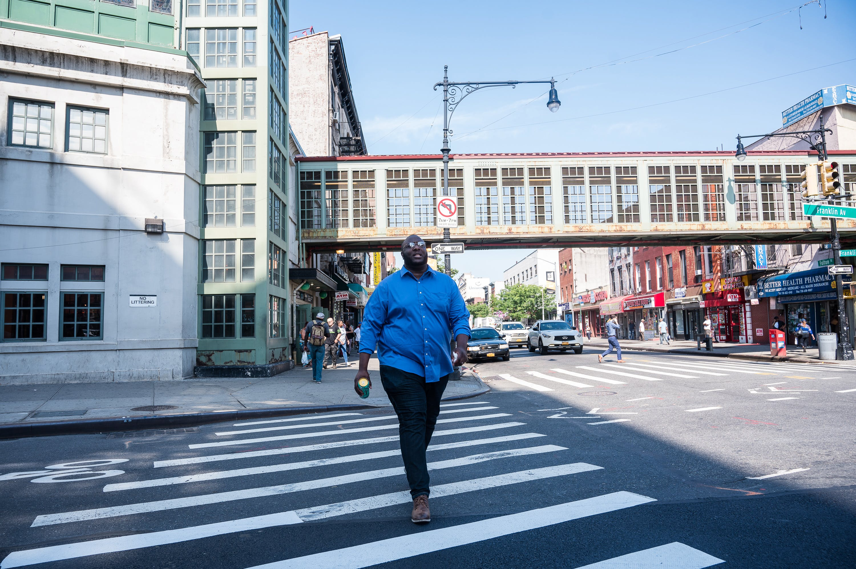 James walks along Fulton Street, a major thoroughfare that divides the Brooklyn neighborhoods of  Clinton Hill and Prospect Heights , on August 19, 2019.