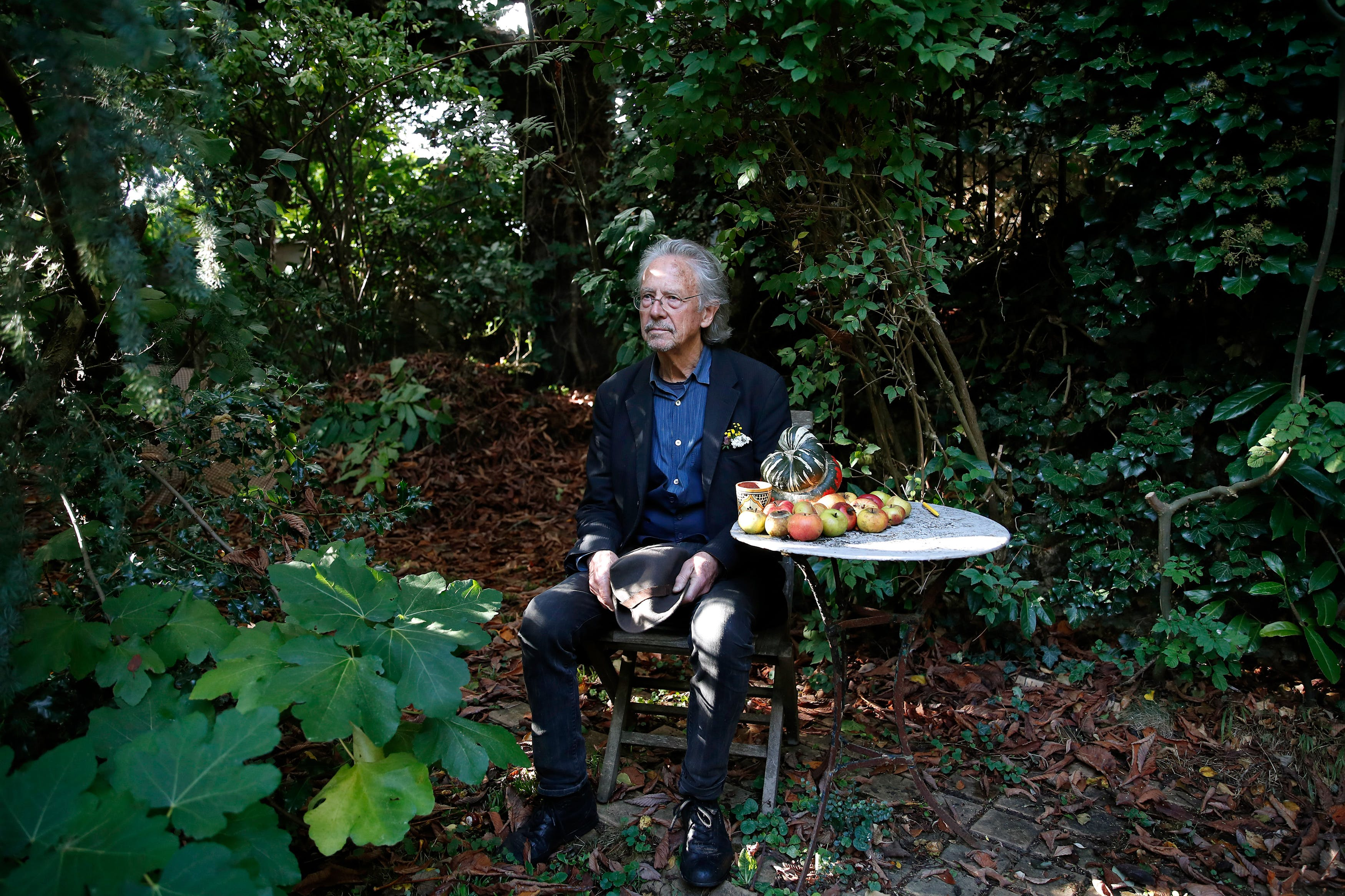 Austrian author Peter Handke sits in this garden at his house in Chaville near Paris, Thursday, Oct. 10, 2019. Handke was awarded the 2019 Nobel Prize in literature earlier Thursday. (AP Photo/Francois More)