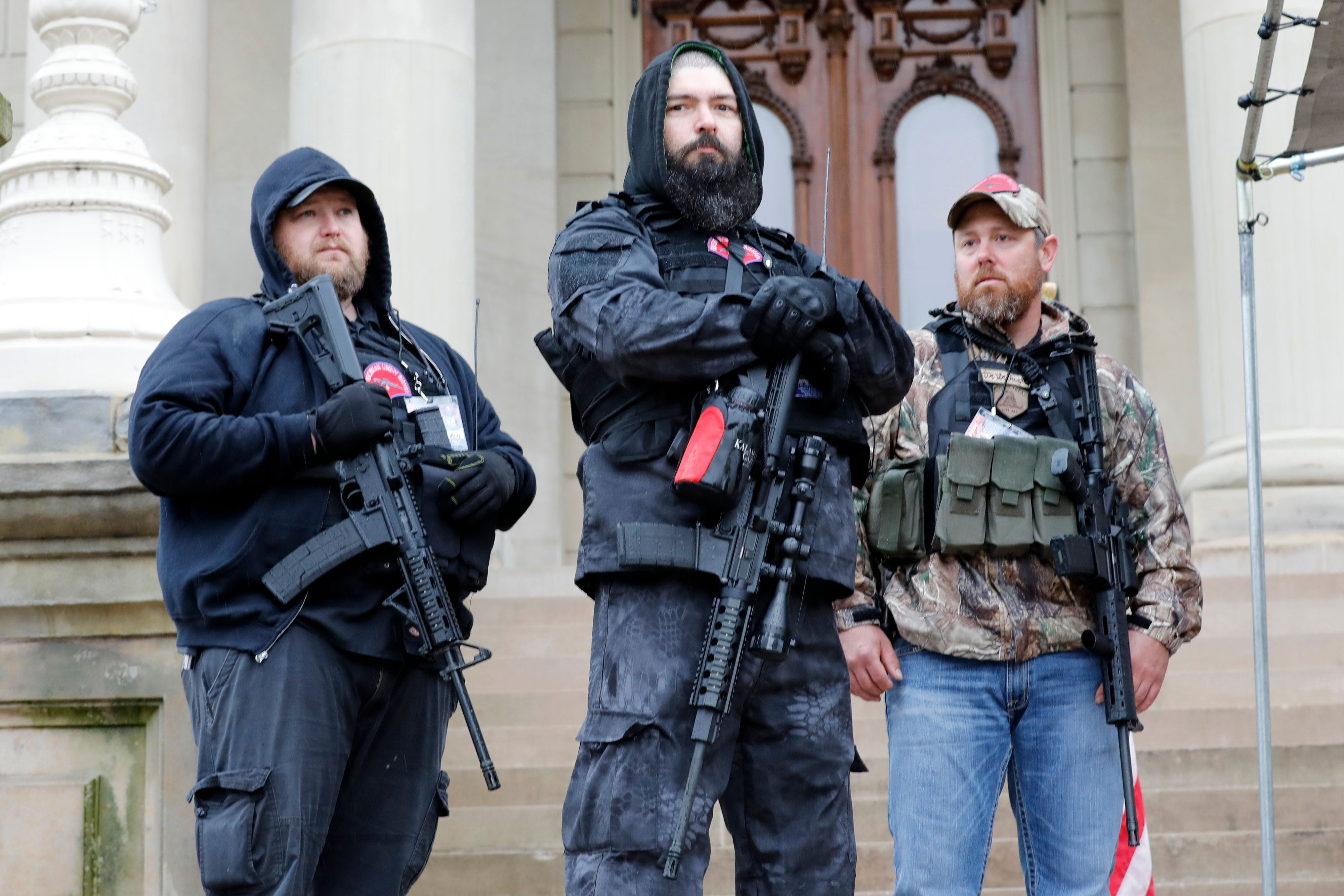 """Armed men take part in an """"American Patriot Rally,"""" organized on April 30, 2020, by Michigan United for Liberty on the steps of the Michigan State Capitol in Lansing, demanding the reopening of businesses. (Photo by JEFF KOWALSKY / AFP) (Photo by JEFF KOWALSKY/AFP via Getty Images)"""