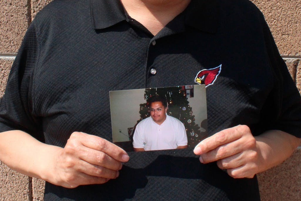 Auska Mitchell holds a photograph of his nephew, Lezmond Mitchell, on Aug. 21, 2020, in the Phoenix area.