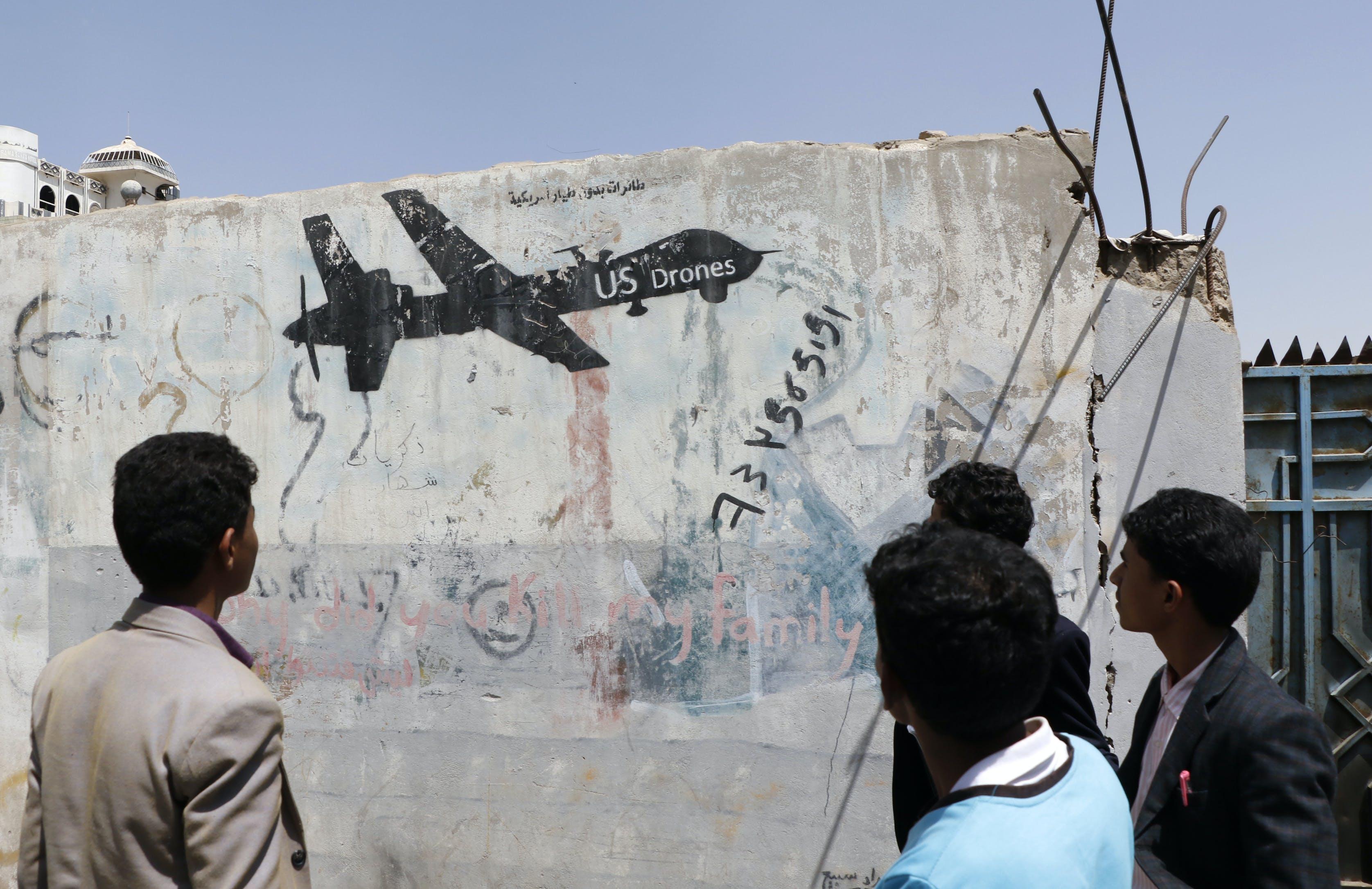 A Yemeni man looks at graffiti protesting against US drone strikes on September 19, 2018 in Sana'a, Yemen.