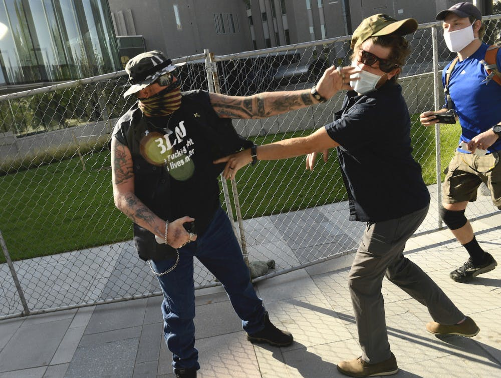 "DENVER, COLORADO - OCTOBER 10: A man punches another man after a rall in Denver, Colorado, on October 10, 2020. The man on the left side of the photo was supporting the ""Patriot Rally"". He engaged with the man on the right, hit him in the face and sprayed him with mace. The man at right, then shot and killed the protester at left. At the time two rallies, one right-wing and another left-wing, were taking place near one another. Denver Channel 9News has confirmed that the man who did the shooting was a private security guard contracted by them and is in custody after the shooting. It has been confirmed the guard was contracted through Pinkerton for the station. (Photo by Helen H. Richardson/MediaNews Group/The Denver Post via Getty Images)"