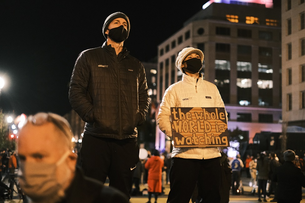 """A person holds a sign that reads """"The Whole World Is Watching"""" at the Black Lives Matter Plaza on 3 November 2020 in Washington, DC"""