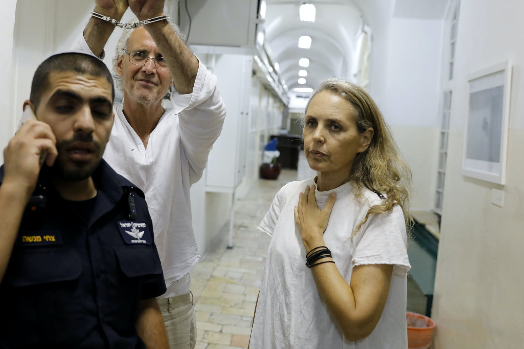 American-French law professor Frank Romano (C) who was arrested by Israel while protesting against the demolition of a Palestinian village in the West Bank gestures at the Jerusalem court on September 16, 2018.To his right is his lawyer Gaby Lasky. - US-born Romano, who teaches law at the Paris Nanterre University, was detained two days ago while taking part in a demonstration at the Bedouin village of Khan al-Ahmar, east of Jerusalem. His lawyer said today that he will be deported. (Photo by Ahmad GHARABLI / AFP)        (Photo credit should read AHMAD GHARABLI/AFP via Getty Images)