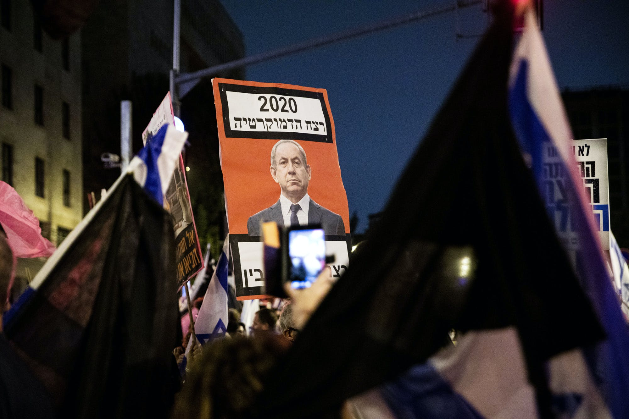 JERUSALEM - OCTOBER 31: Israeli protestors gather on Saturday night in protest against Prime Minister Benjamin Netanyahu demanding his resignation over corruption cases and his failure to combat the new type of coronavirus (Covid-19) pandemic in West Jerusalem on October 31, 2020. (Photo by Mostafa Alkharouf/Anadolu Agency via Getty Images)