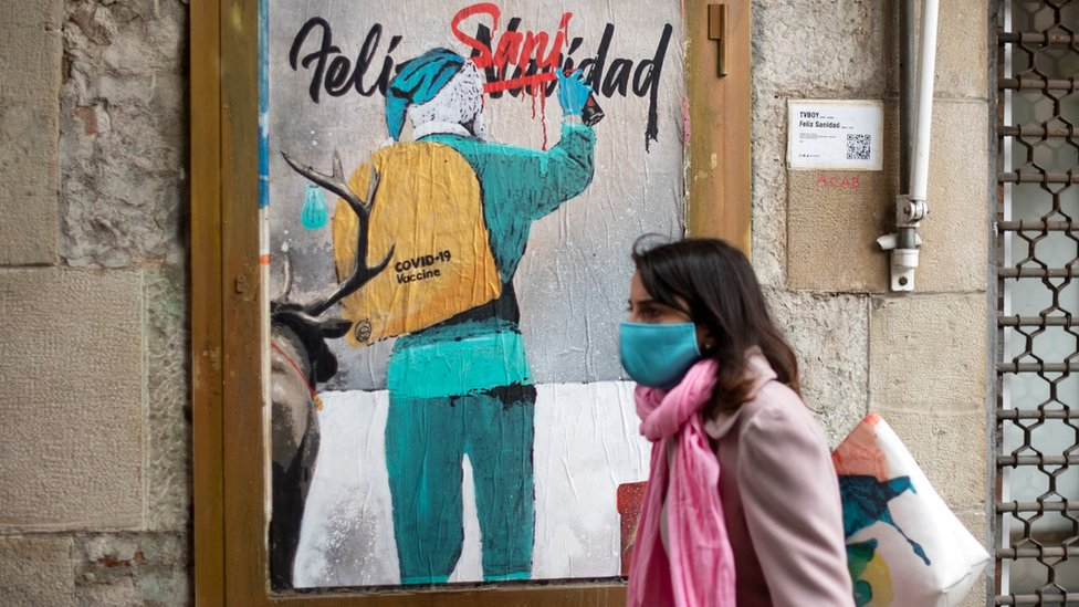 A woman walks past a new work by Italian street artist TvBoy depicting Santa Claus carrying the Covid-19 vaccine in his sack