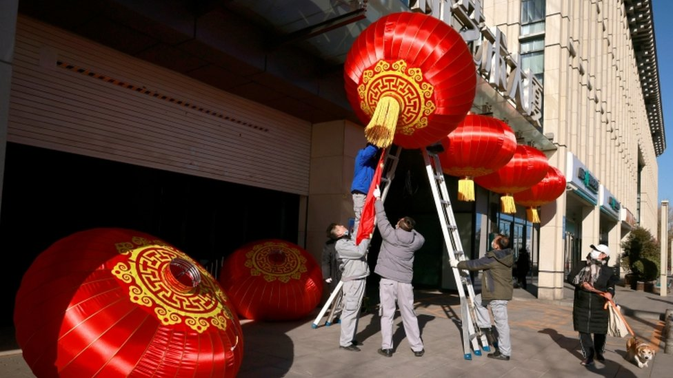 Men hang red lanterns marking New Year and Lunar New Year festivities following the outbreak of Covid-19 in Beijing, 31 December 2020