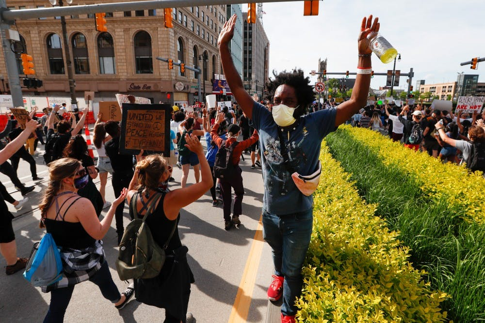 Tristan Taylor leads protesters during a march on Woodward Avenue in Detroit, Wednesday, June 3, 2020, over the death of George Floyd, a black man who was in police custody in Minneapolis. (AP Photo/Paul Sancya)