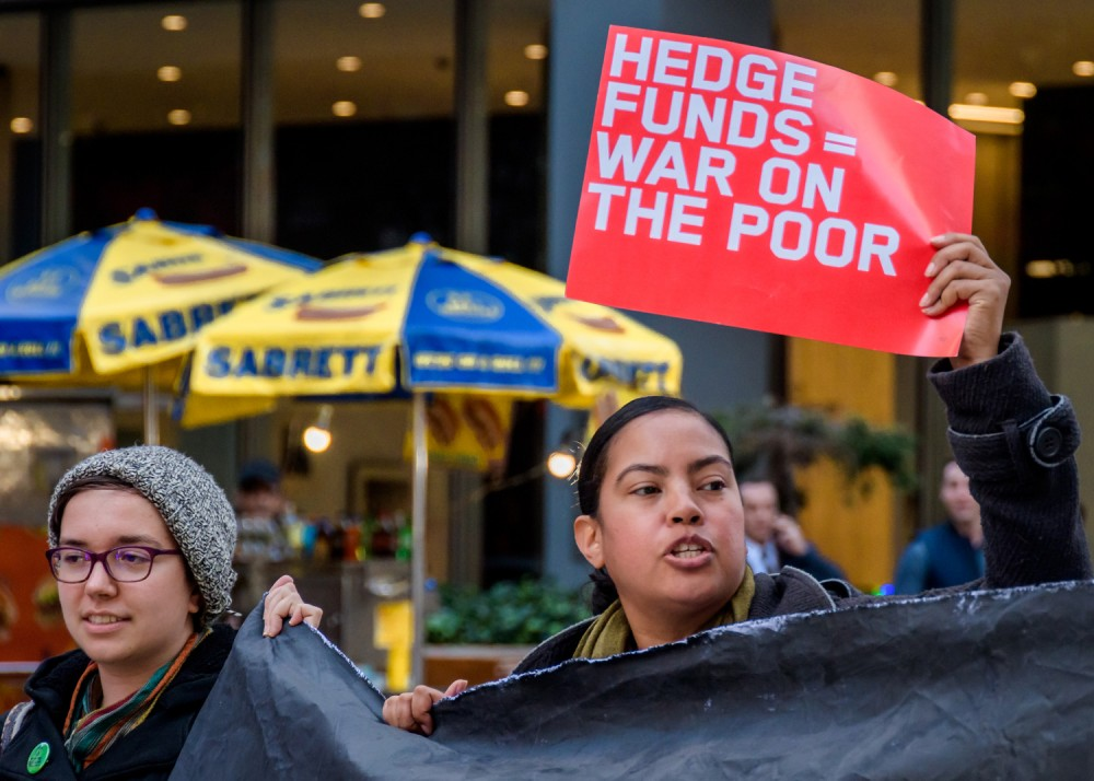 A protester holding a sign reading: HEDGE FUNDS=WAR ON THE