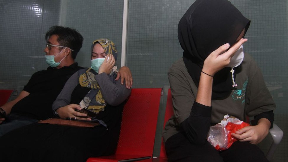 Relatives of passengers on board missing Sriwijaya Air flight SJY182 wait for news at the Supadio airport in Pontianak on Indonesia's Borneo island on January 9, 2021, after contact with the aircraft was lost shortly after take-off from Jakarta.
