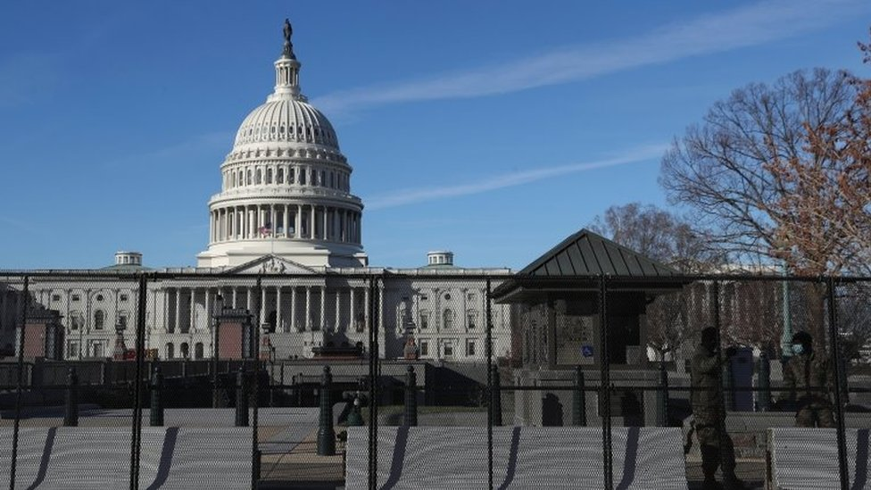 Members of the National Guard stand next to a fence and barricades set up around the U.S. Capitol building in Washington