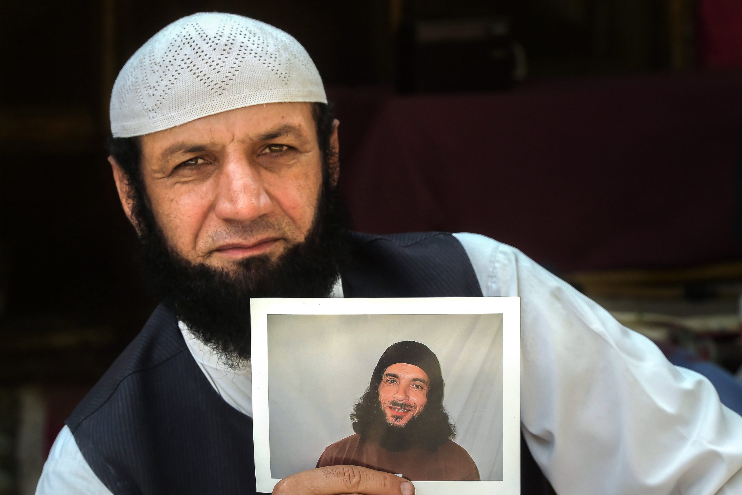 In this picture taken on September 25, 2020, Afghan refugee Roman Khan displays a photograph of his brother Asadullah Haroon, who is detained in Guantanamo Bay detention camp, during an interview with AFP in Shamshatu refugee camp near Pakistan's northwestern city of Peshawar. - Hundreds of prisoners including senior Taliban leaders have been released from the notorious US military detention centre, but Asadullah Haroon, who has never been charged with a crime, remains. (Photo by Abdul MAJEED / AFP) / To go with 'AFGHANISTAN-GUANTANAMO-PRISONERS', FOCUS by David Stout and Sajjad Tarakzai (Photo by ABDUL MAJEED/AFP via Getty Images)