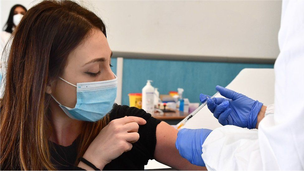 A woman is vaccinated against Covid-19 with the AstraZeneca vaccine in Genoa, Italy, 10 March 2021.