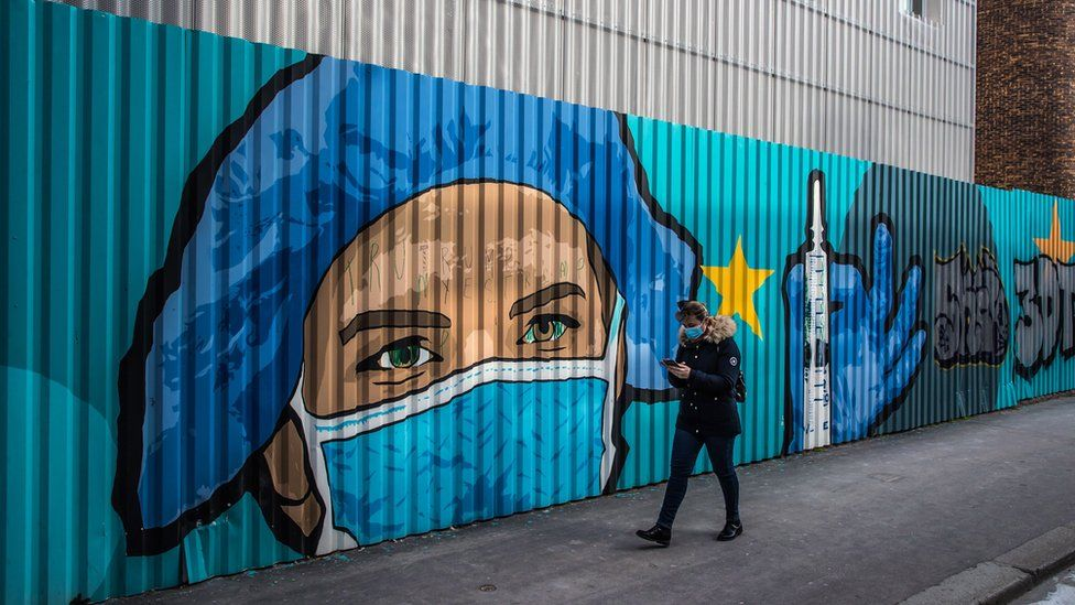 A pedestrian walks past a street-art mural by French artist JBC, in tribute to health workers representing a nurse wearing a protective face mask in front of a hospital in Paris, France, 20 March 2021