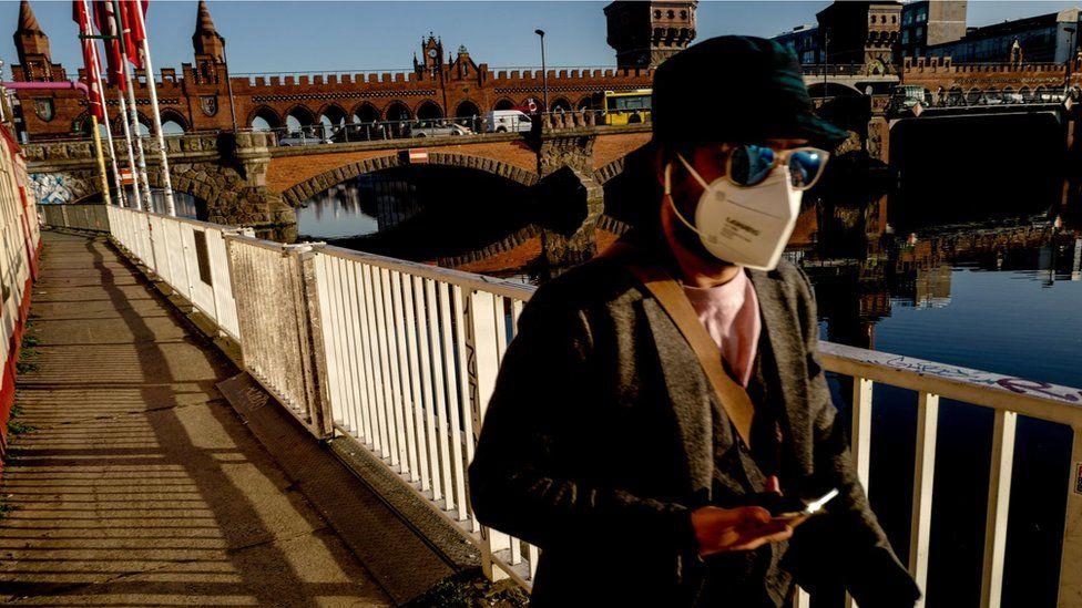 A woman in Berlin in a mask walking near the Oberbaum Bridge (2 March)
