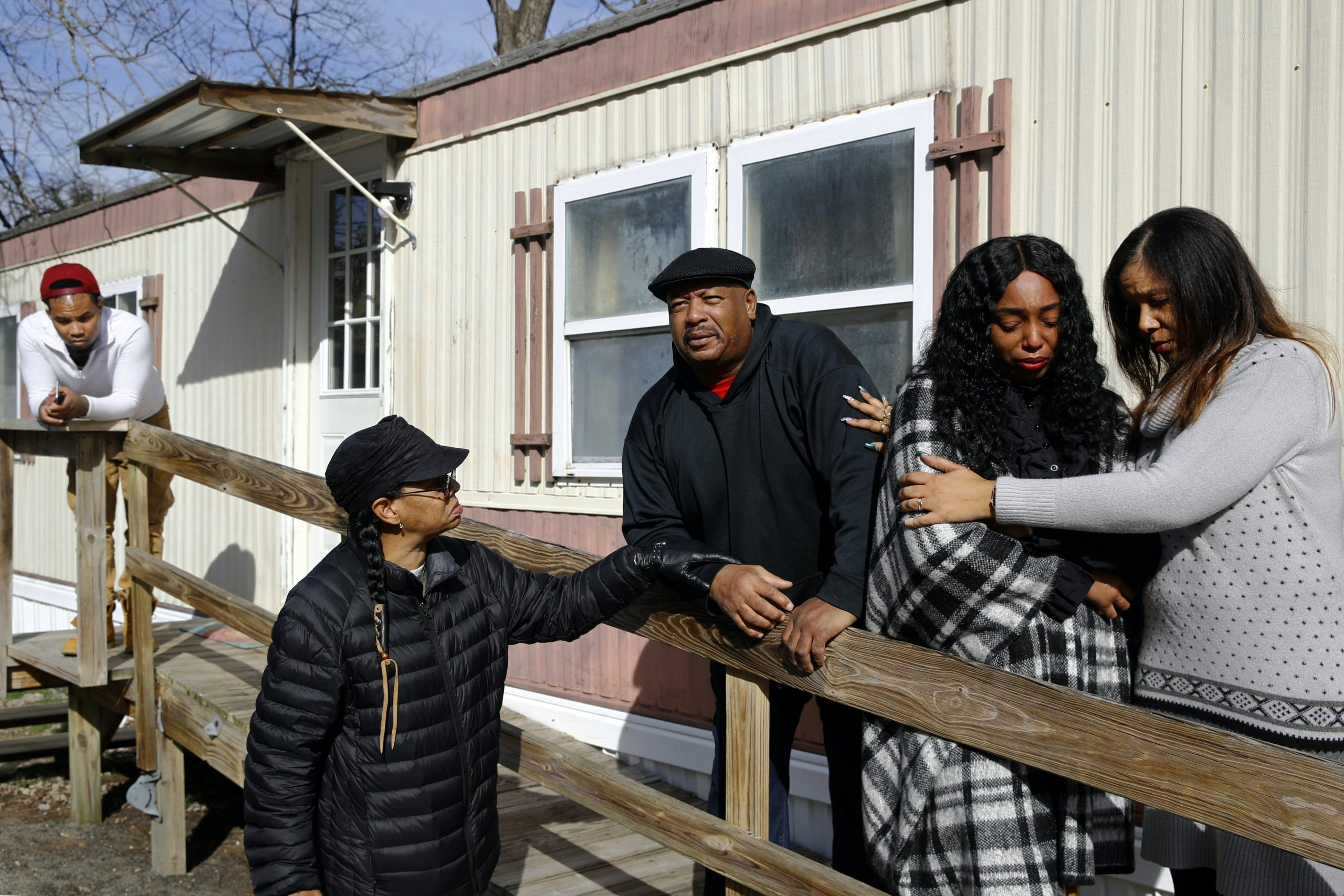 In this Jan. 28, 2019, photo, Brandon Jackson, from far left, Kym Lofland, Antone Black, Monique Sorrell and LaToya Holley stand on a ramp where a struggle among their family member Anton Black and three police officers and a civilian occurred before his death outside the home in Greensboro, Md. The family isn't satisfied by the conclusions of a county prosecutor, who isn't pursuing criminal charges in Black's death, or the medical examiner who ruled it accidental. They're calling for a federal investigation and appealing for help from Gov. Larry Hogan, who already has expressed a personal interest in the case. (AP Photo/Patrick Semansky)